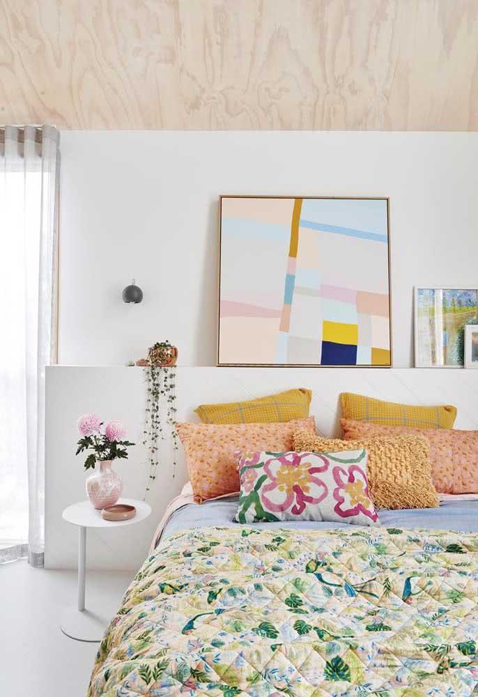 Roupa de cama colorida em diferentes tons, entre eles o amarelo pastel que combina diretamente com o quadro na parede