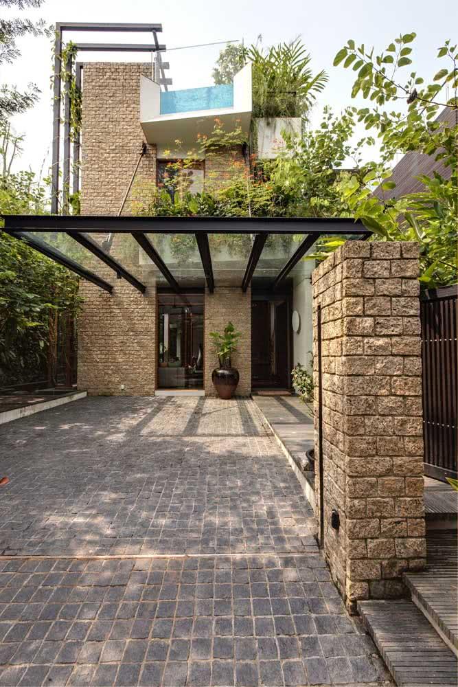 Pergolado de vidro para garagem. A estrutura metálica ganhou apoio nos pilares de tijolos