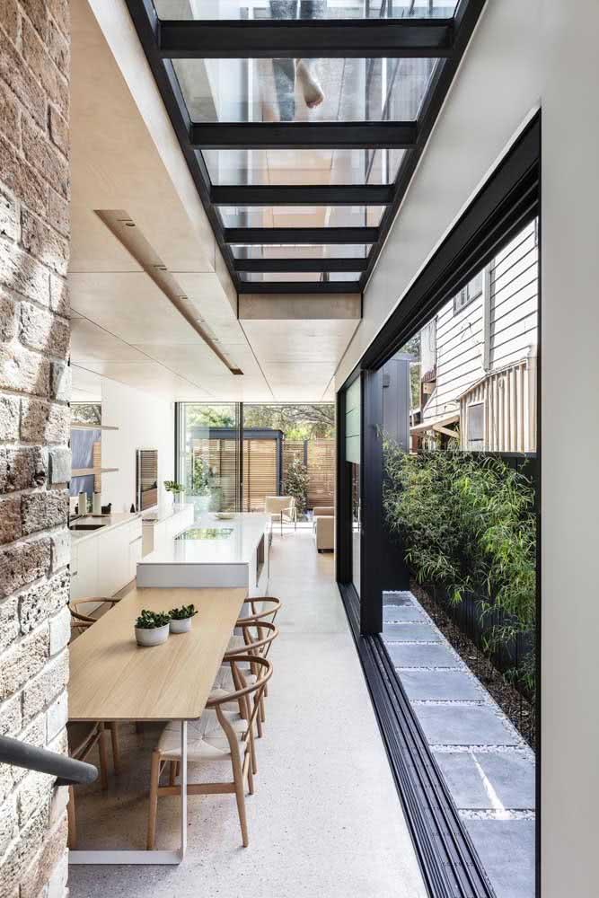 Pergolado de vidro para iluminar o corredor que faz a integração entre a área interna e externa