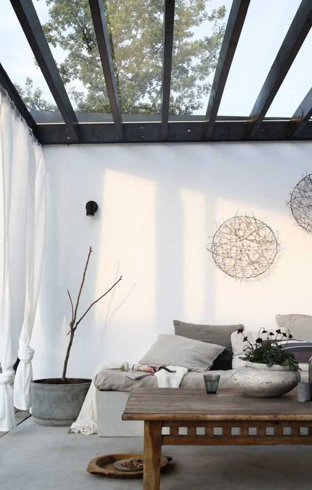 Já na sala minimalista, a proposta é usar o pergolado metálico preto com cobertura de vidro