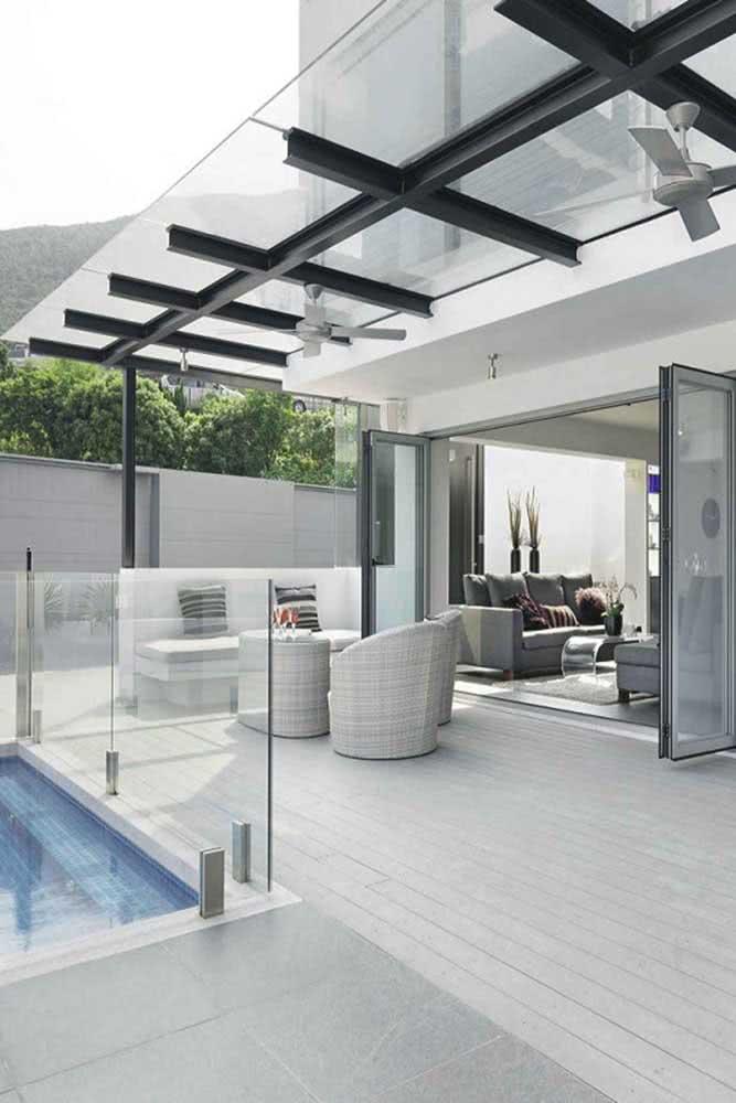 Pergolado de vidro moderno para acompanhar a varanda junto à piscina