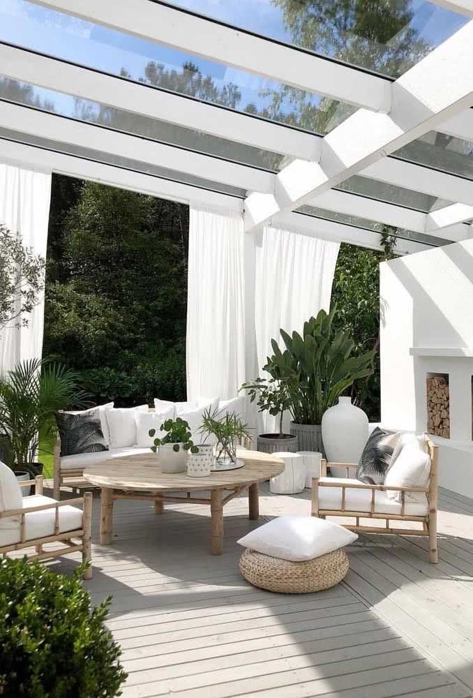 Pergolado de vidro para manter a luminosidade e cortinas para garantir a privacidade