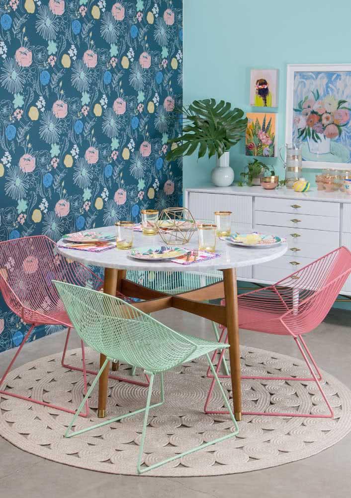 Esta sala de jantar feminina recebeu cadeiras metálicas com tons pastéis que combinam com os demais itens decorativos e a até a pintura da parede.