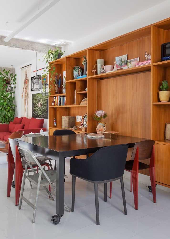 Mesa de madeira escura recebe cadeiras de diferentes cores e diferentes tamanhos.