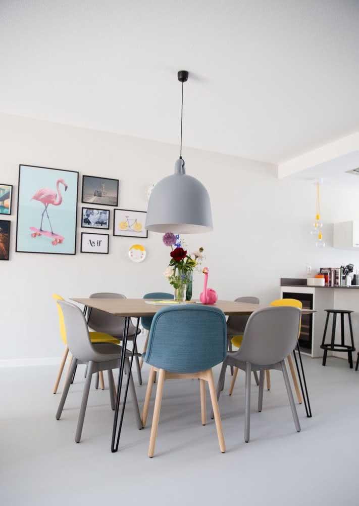 Mesa de jantar na cozinha com cadeiras nas cores: cinza, azul e amarelo.