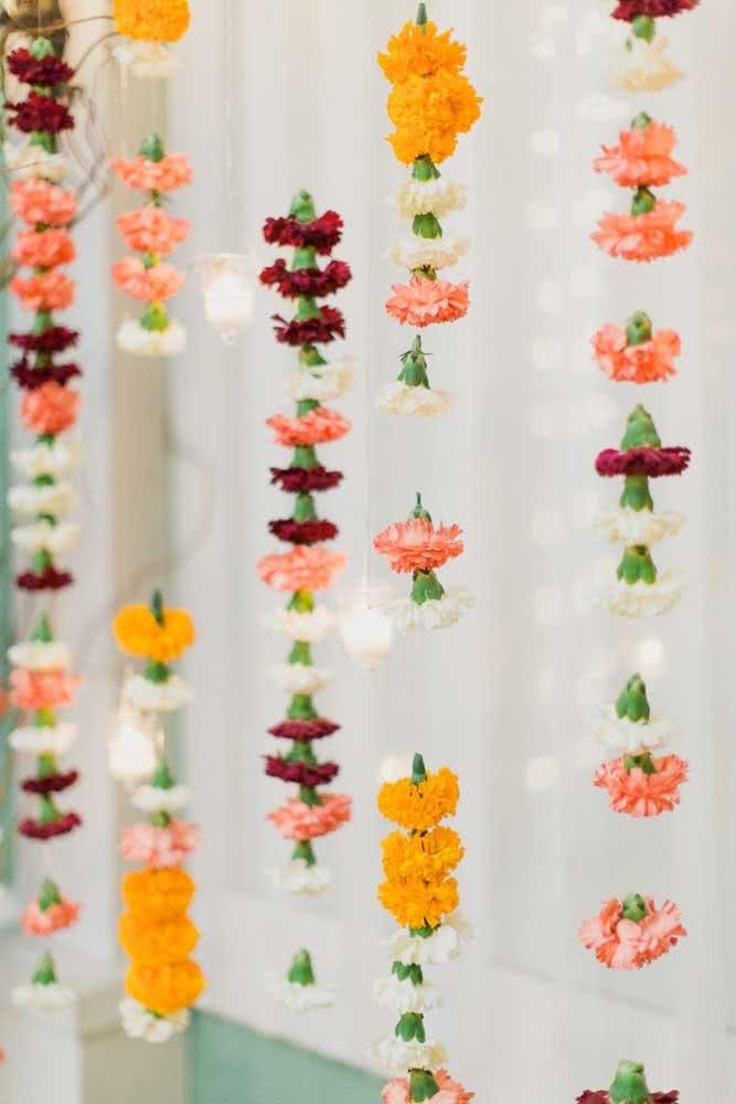 Já aqui, a cortina foi feita com cravos coloridos suspensos em fios de nylon
