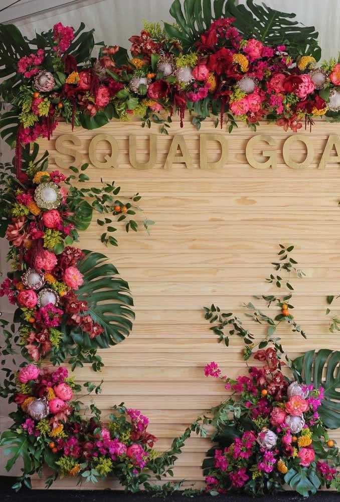Que tal um painel de flores tropicais? A madeira ajuda a trazer o clima rústico para a decoração