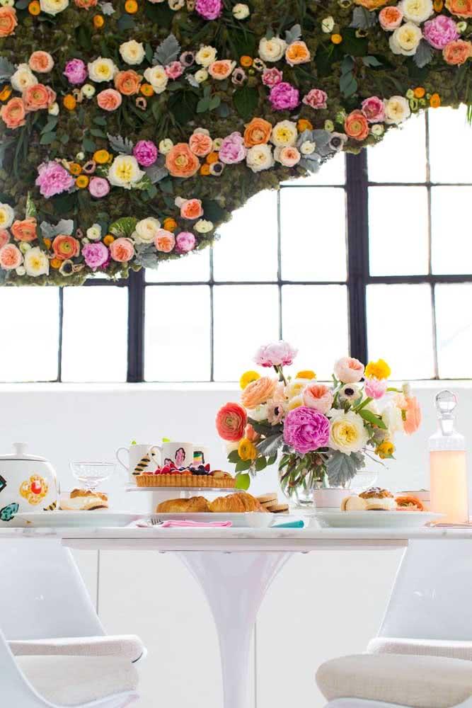 Painel de flores coloridas em contraste com a decoração branca da festa