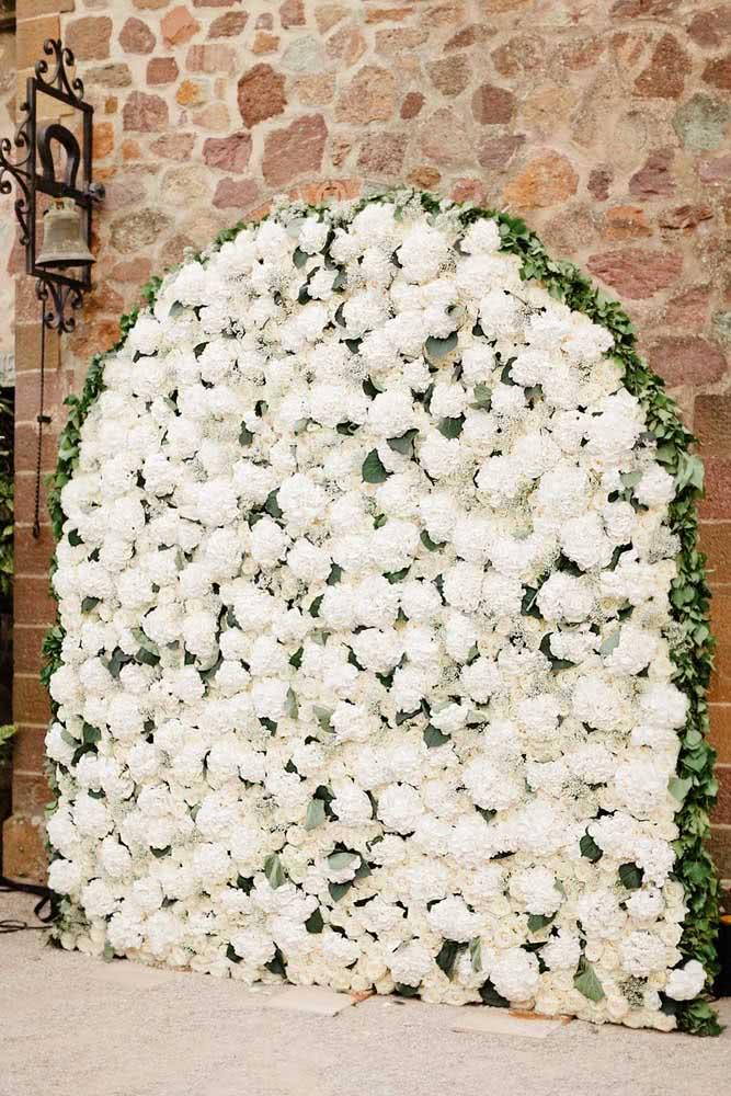 O lindo contraste entre as flores brancas e a parede de tijolos