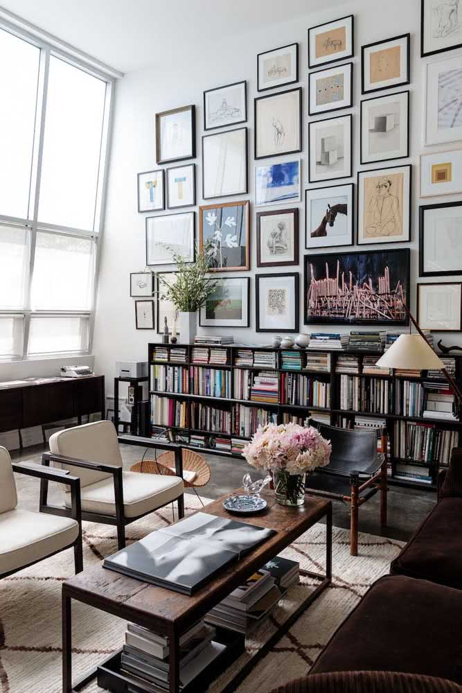 Livros e quadros preenchem a parede da sala de pé direito alto