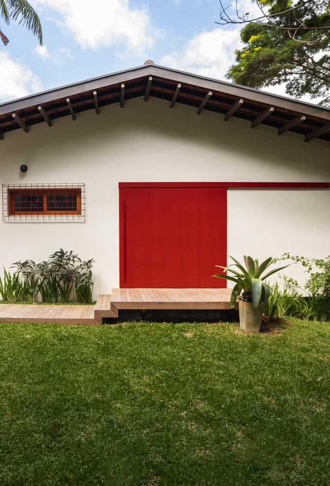 Fachada de casa simples e pequena valorizada pelo detalhe da porta vermelha