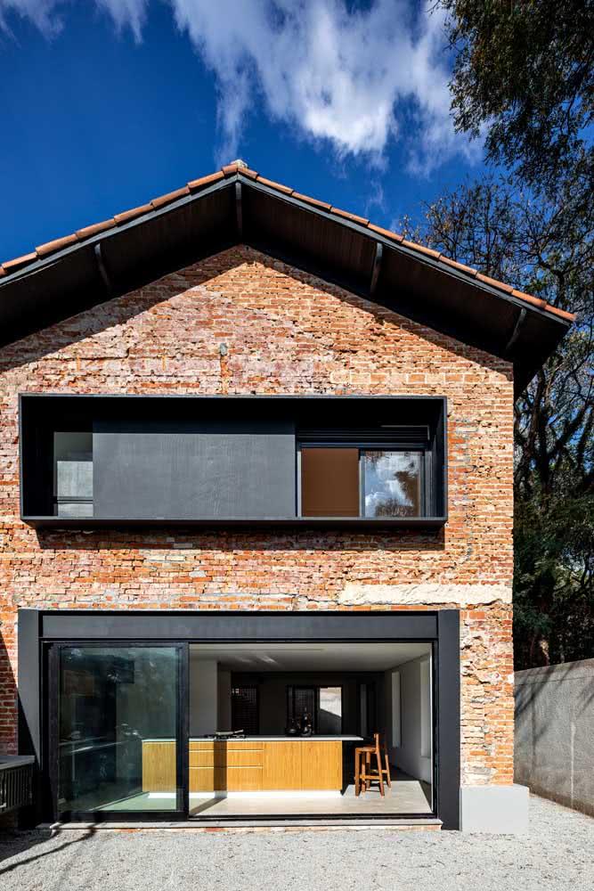Casa por fora de tijolinhos e esquadrias metálicas pretas