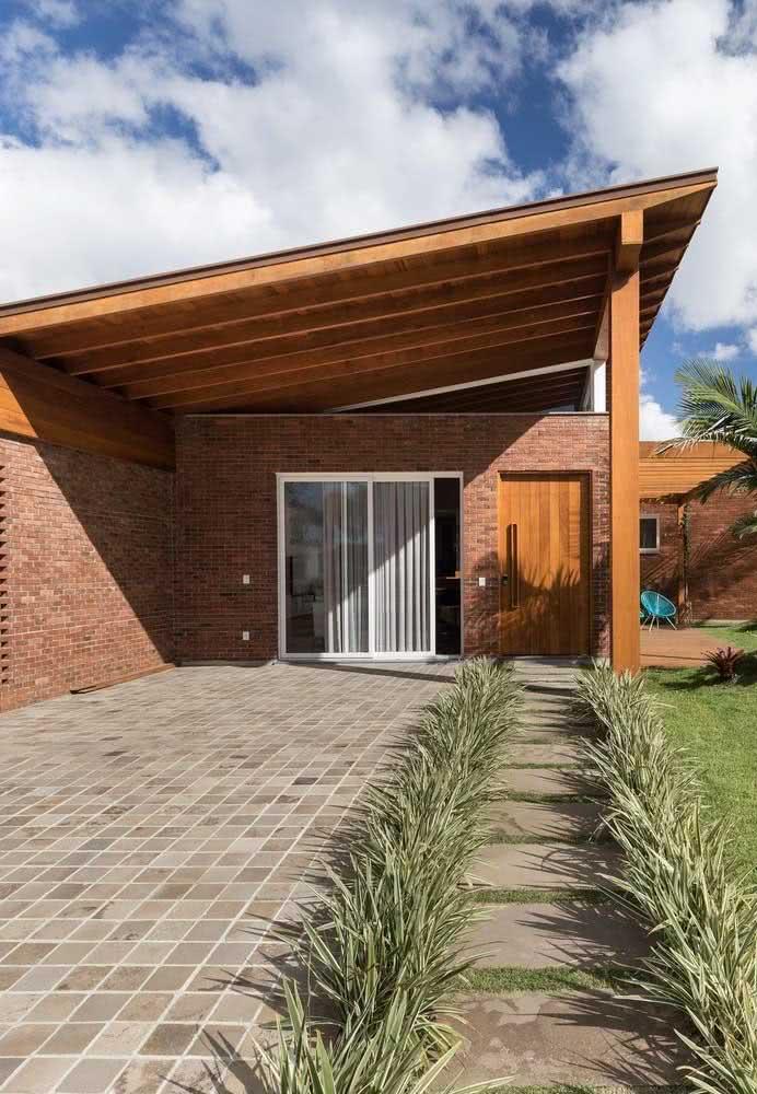 Casa rústica por fora com acabamento em madeira e tijolinhos