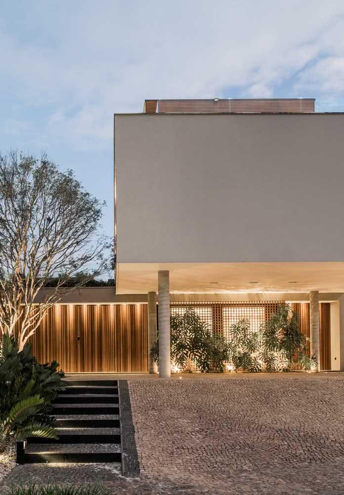 Fachada de casa moderna e iluminada com jardim