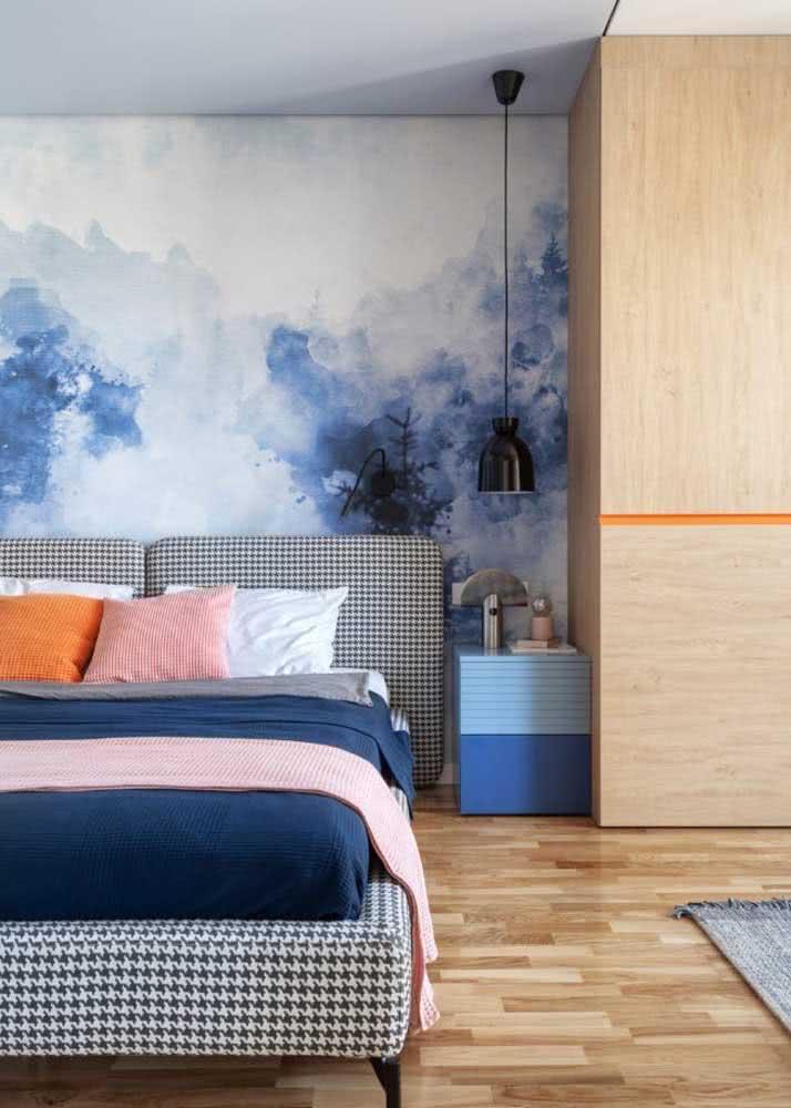 Degradê entre o azul e o branco neste papel de parede no quarto de casal.