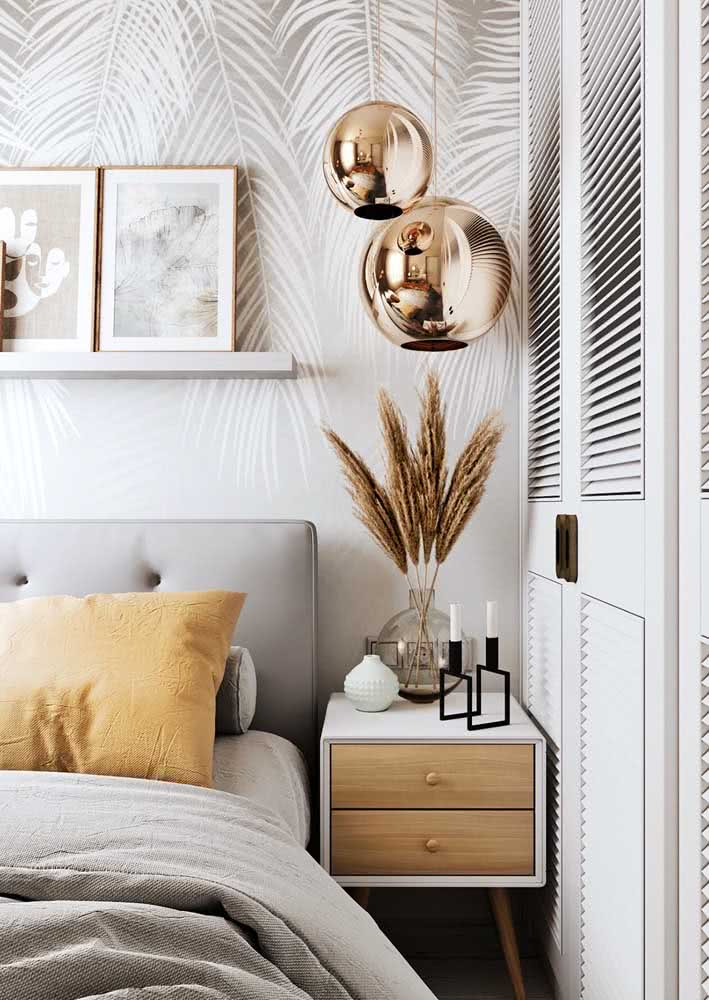 Folhas de palmeiras pendentes em papel de parede com tonalidade de cor suave.