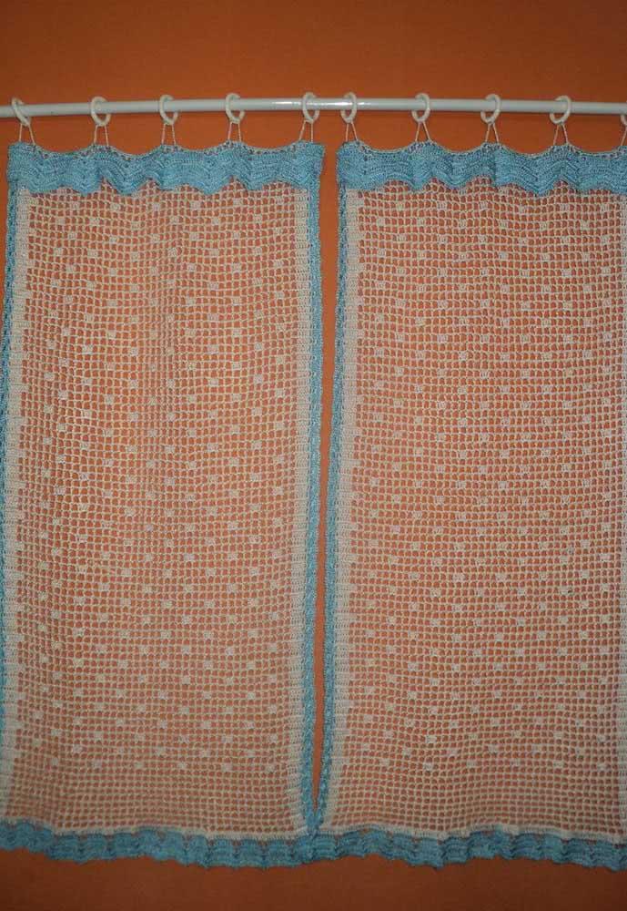 Cortina de crochê pequena com borda em barbante azul e centro com pequenos pontos.