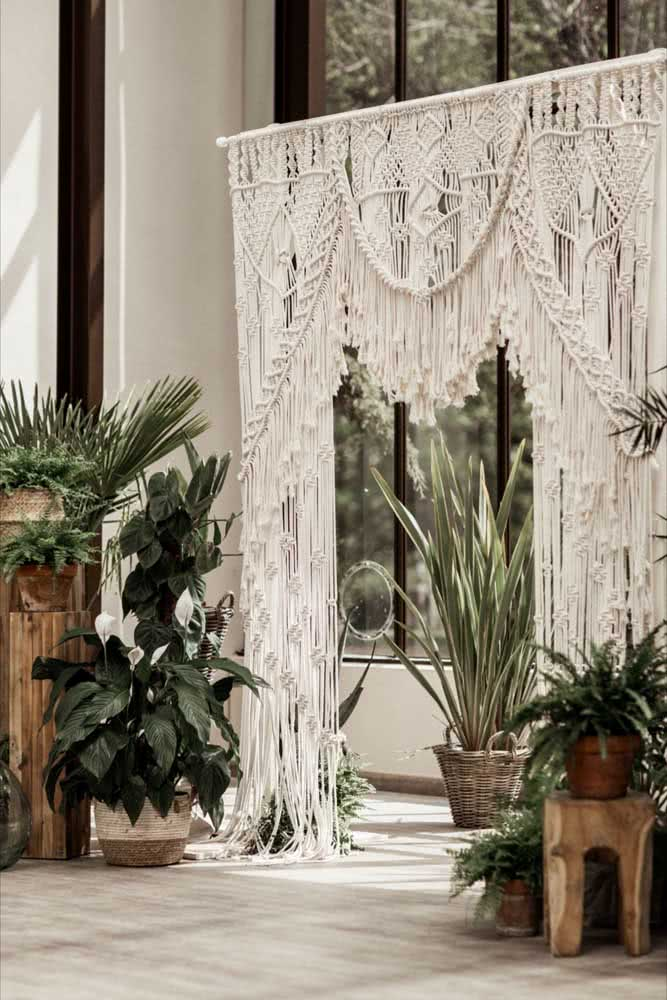 Cortina de crochê para janela da sala com plantas.