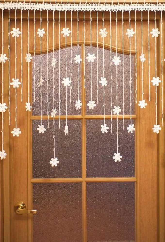 Cortina de crochê delicada para porta com pequenas flores em fios pendentes.
