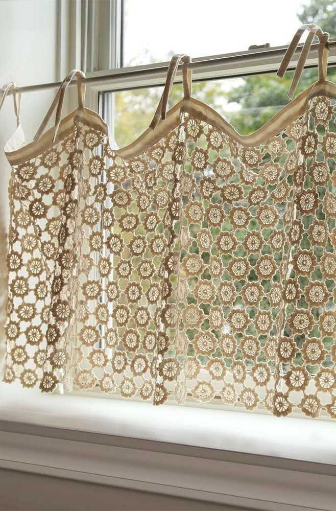 Flores delicadas em cortina de crochê pequena que ocupa metade da janela da casa.