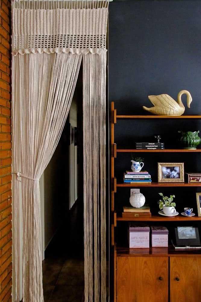 Cortina de crochê extensa com fios de barbante suspensos para separar a sala de outros ambientes.