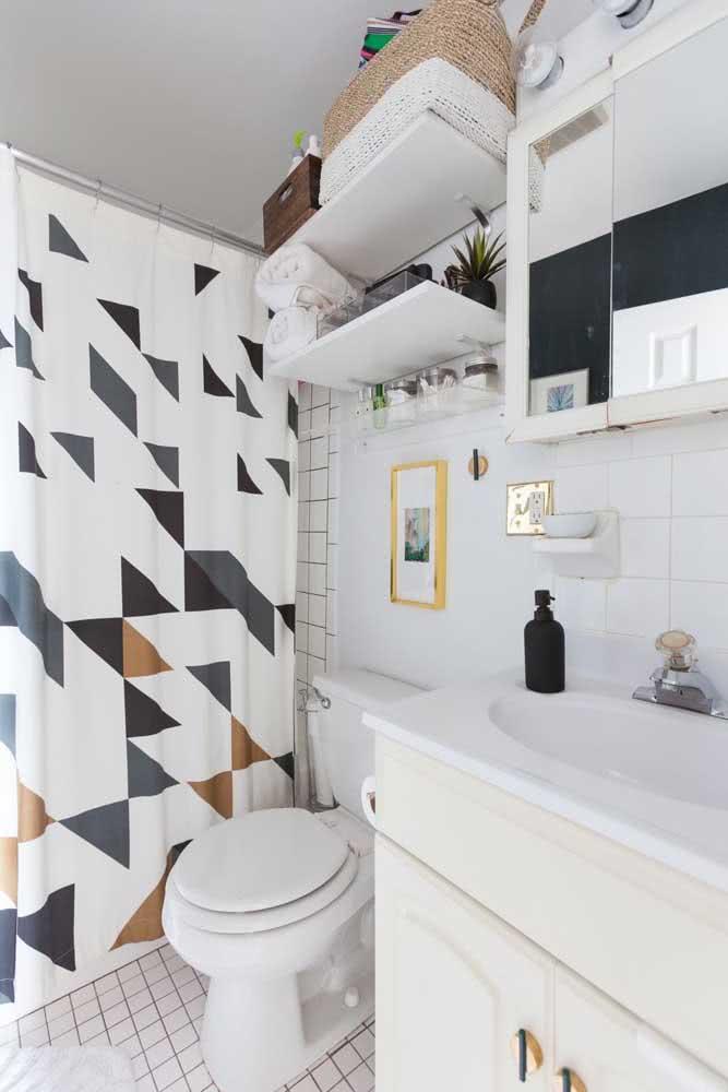Banheiro branco pequeno e toalha de banho com desenhos geométricos.
