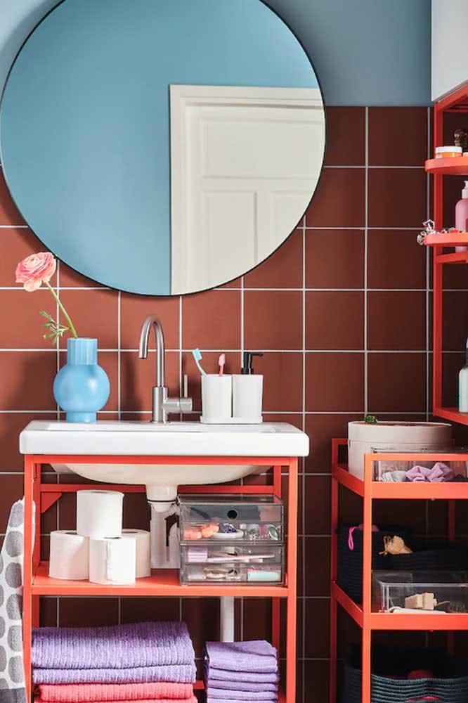 Azulejo cor marsala com pintura azul e grande espelho redondo.