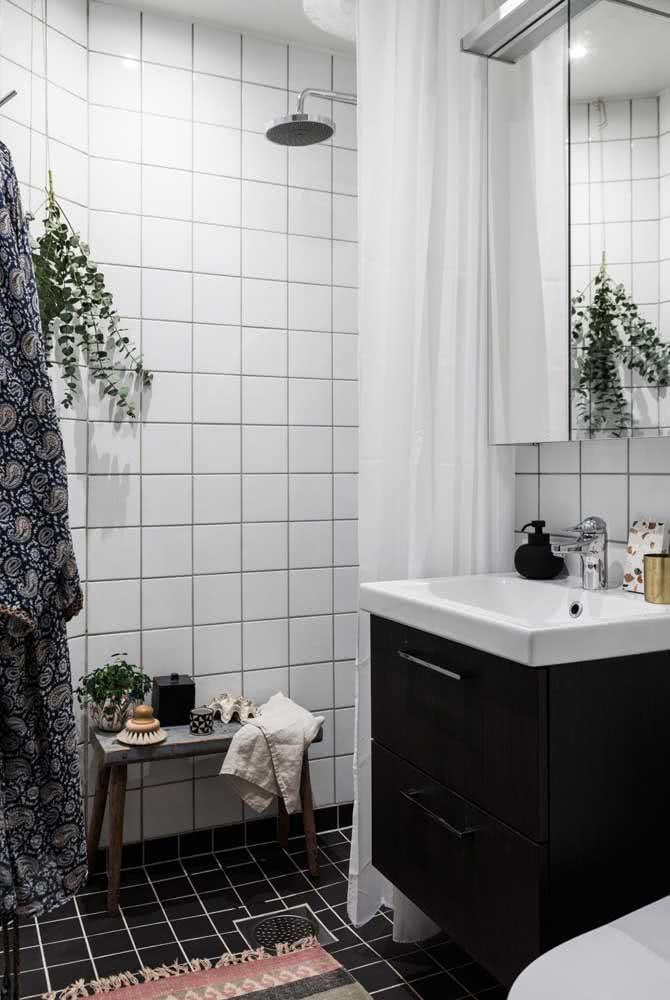 Banheiro com azulejos brancos e gabinete preto embaixo da pia.