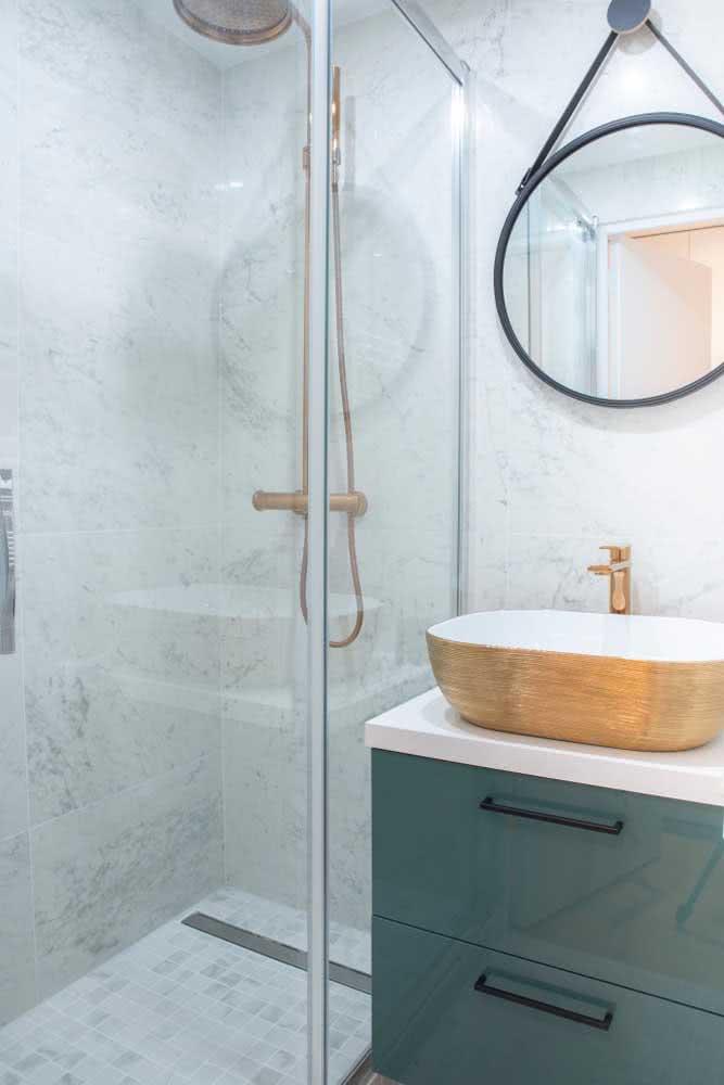 Banheiro com mármore branco, espelho redondo e cuba metálica dourada.