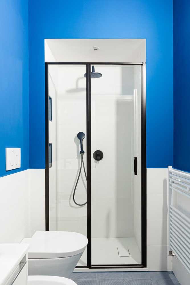 Banheiro azul decorado pequeno com box de vidro.