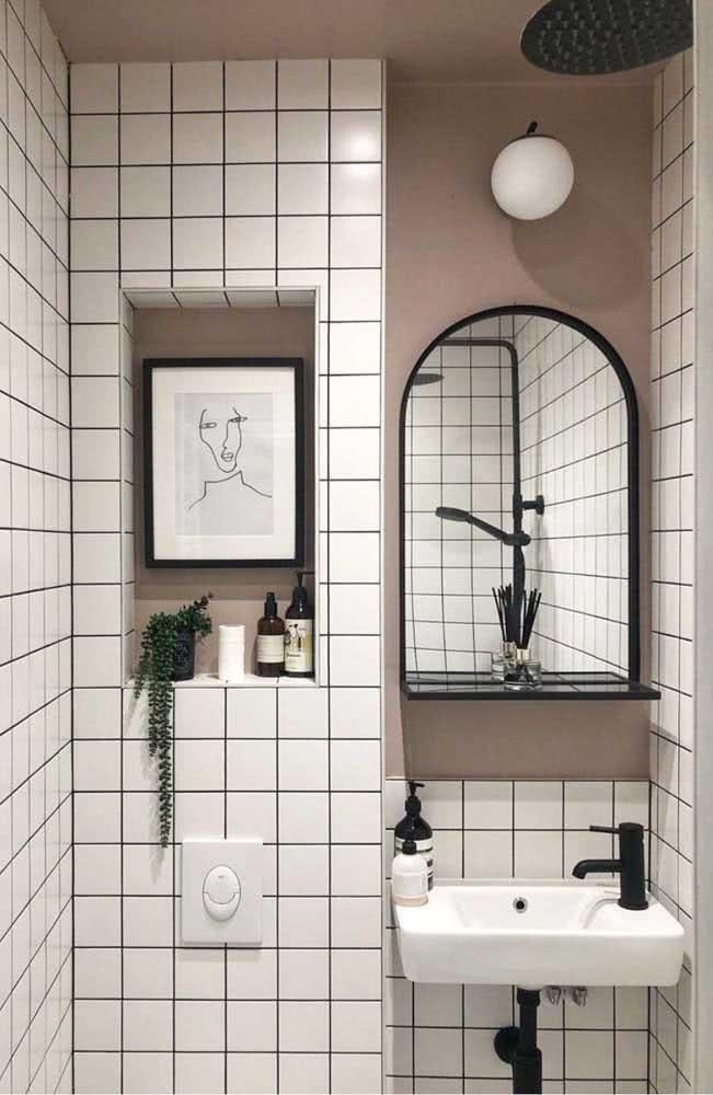 Banheiro com azulejos quadriculados brancos e espelho oval com borda preta.
