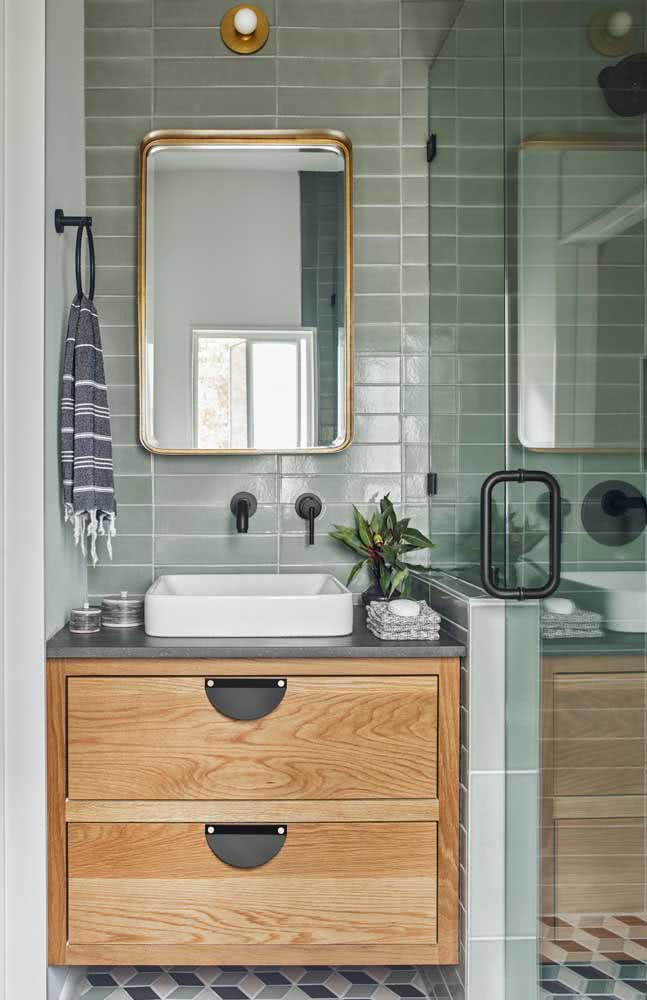 Banheiro com azulejos verdes e box de vidro.
