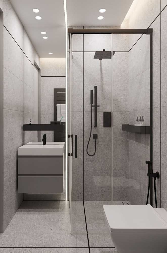 Banheiro simples com material grafite de revestimento e metais pretos no box e na pia.
