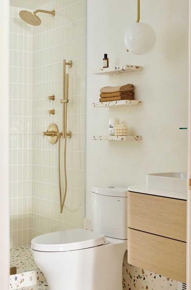 Decoração de banheiro com metais dourados.