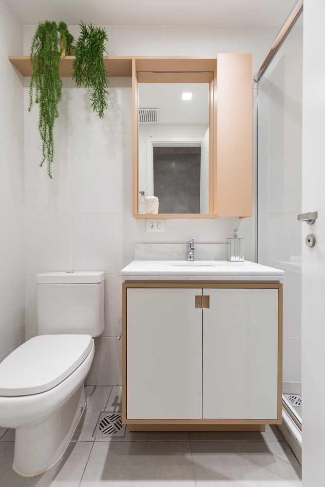 Decoração simples para banheiro com gabinete branco e vasos de plantas.