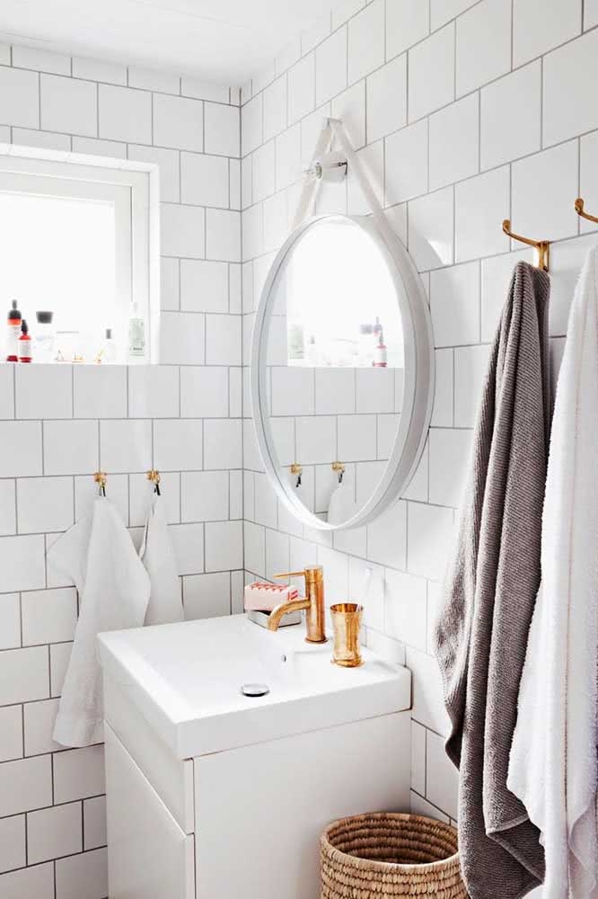 Decoração de banheiro branco com azulejos grandes.