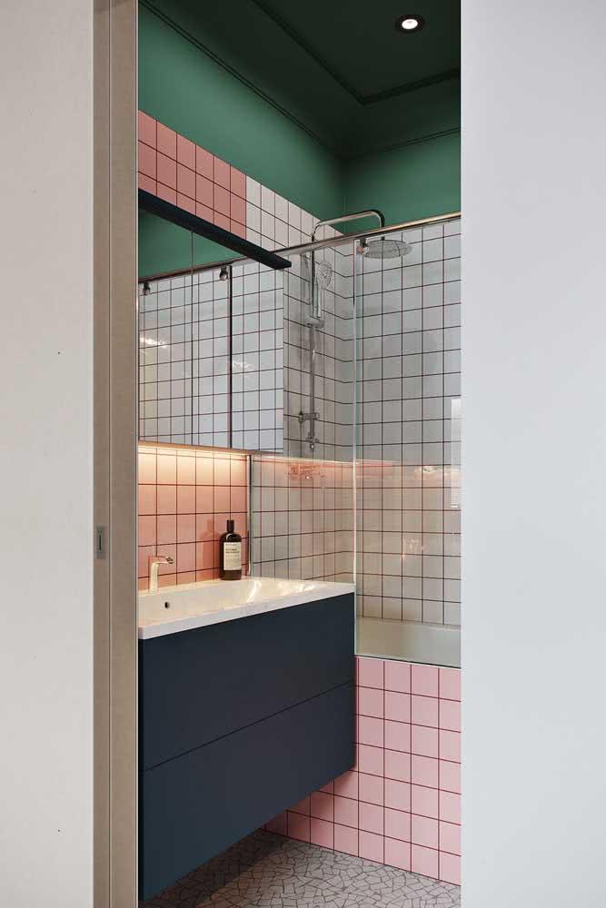 Banheiro com pastilhas brancas, rosas e pintura verde no topo da parede do banheiro.
