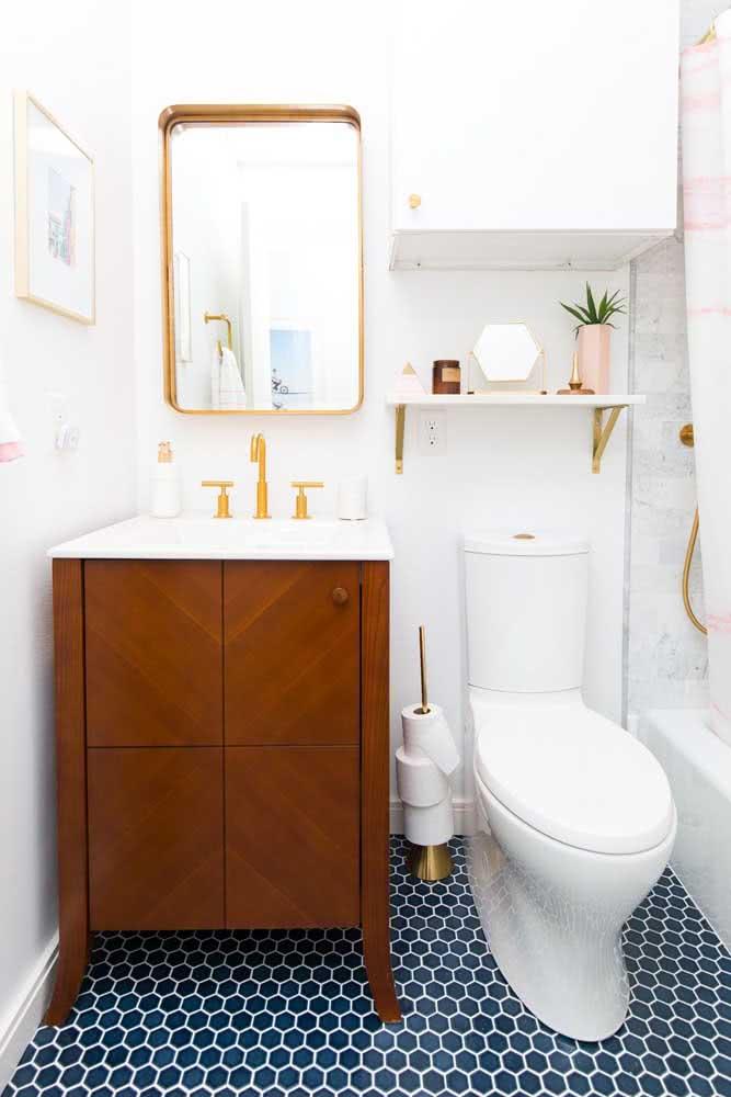 Banheiro branco simples com metais dourados.