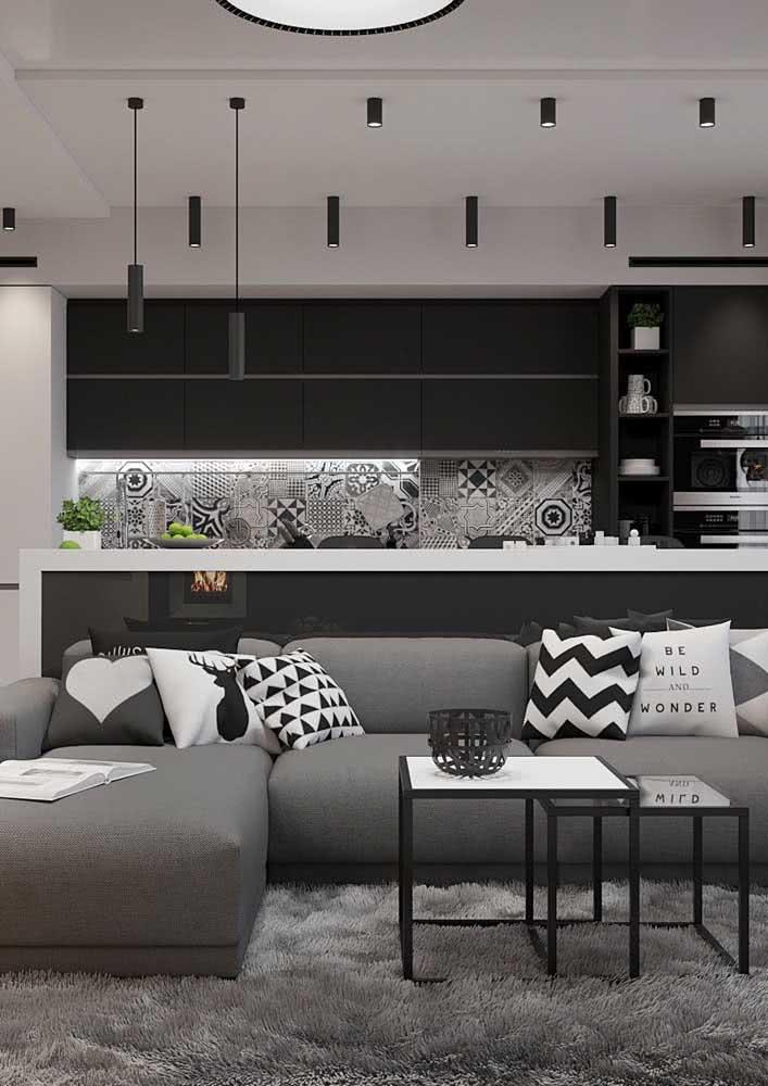 Cozinha com azulejo preto e branca integrada com a sala de estar.