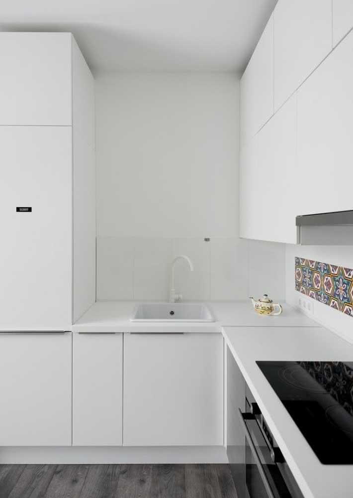 Azulejos hidráulicos em apenas um detalhe desta cozinha toda branquinha.