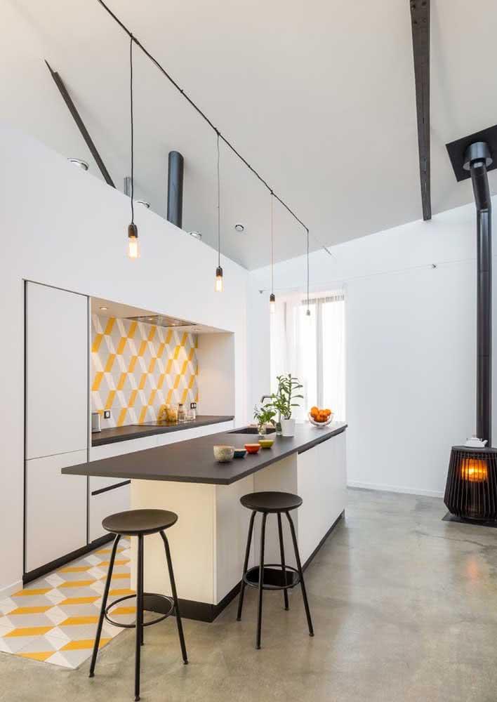 Azulejos com 3 cores: amarelo, cinza e branco no piso e entre a parede da bancada e dos armários da cozinha.