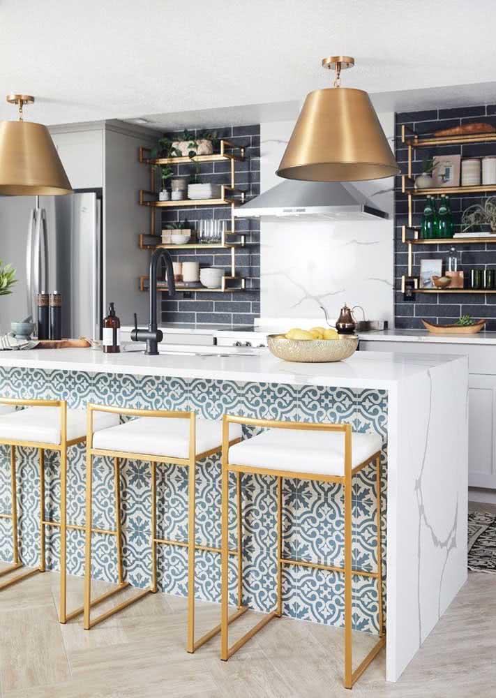 Diferentes tipos de azulejos aplicados na cozinha: na parede, a cor preta com formato retangular no estilo metrô. Na parede da bancada, no estilo ladrilho hidráulico.