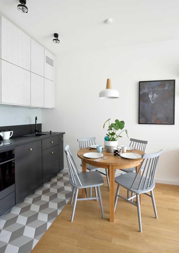 Azulejos no piso da cozinha que é integrada a sala de jantar.