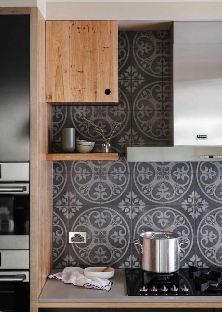 Azulejos escuros na cozinha que segue a mesma tonalidade.
