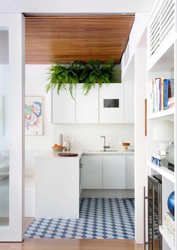 Azulejos hidráulicos no piso desta cozinha toda branquinha.