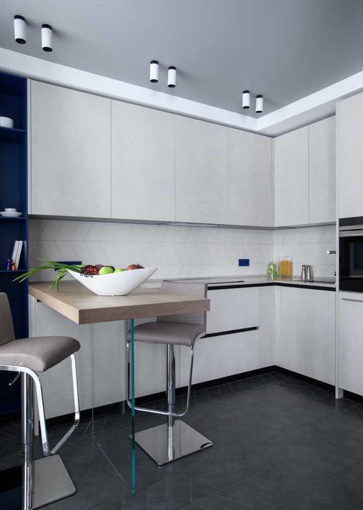 Já esta cozinha clean levou azulejos brancos com desenhos na diagonal entre a parede da bancada e do armário superior.