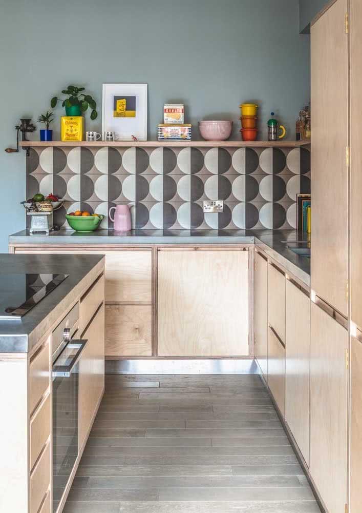 Azulejos com padrão geométrico na parede desta cozinha, somente entre a bancada e a prateleira.