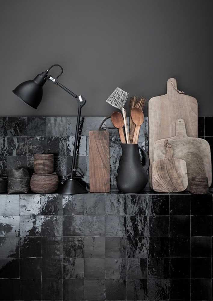 Azulejos escuros na parede da cozinha que é utilizada como prateleira.