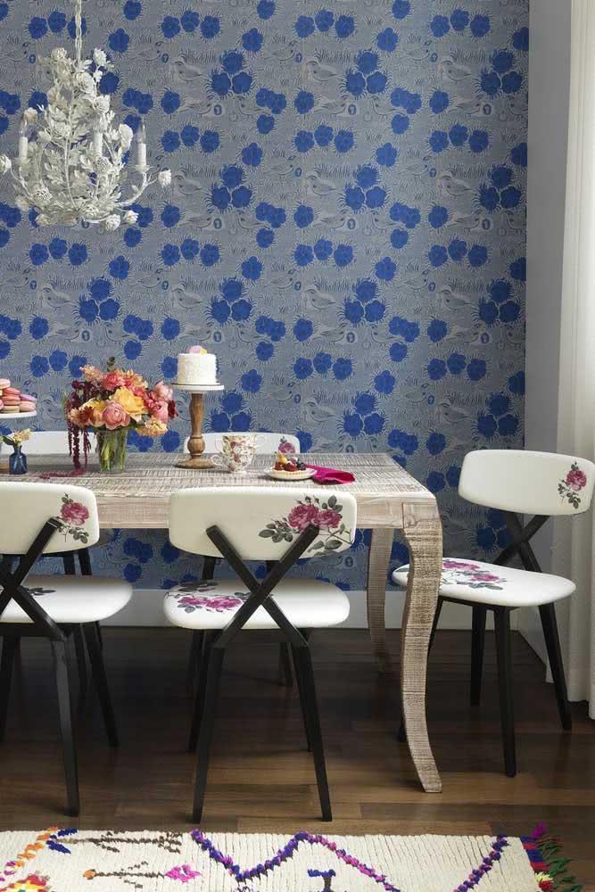 Nessa sala de jantar, as flores estão no papel de parede e no estofado das cadeiras