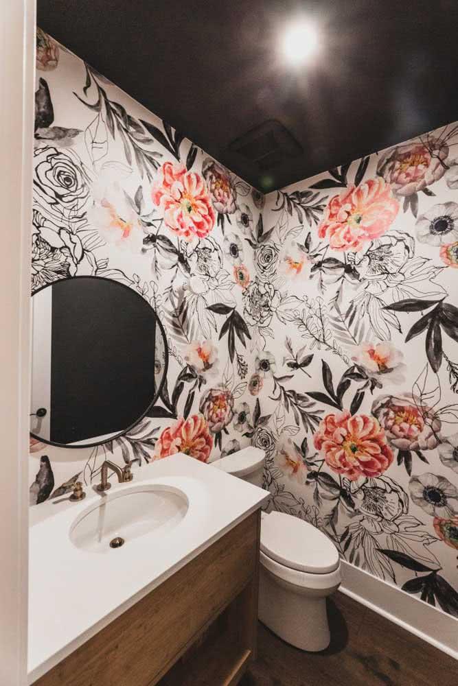 Já nesse outro lavabo, a ideia foi trazer um papel de parede floral de fundo branco para contrastar com o teto preto